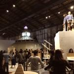 Marcello Maloberti_01, La voglia matta, 2013, masso di marmo, teli mare, fantine, masso 3x2x2 m; Bolide #1,#2,#3...#55, 2013, tavoli in legno, specchi, cinture, meloni, performance/sculture. Courtesy l'artista e Galleria Raffaella Cortese, Milano. Foto Lavinia Collodel (veduta della performance durante il vernissage)
